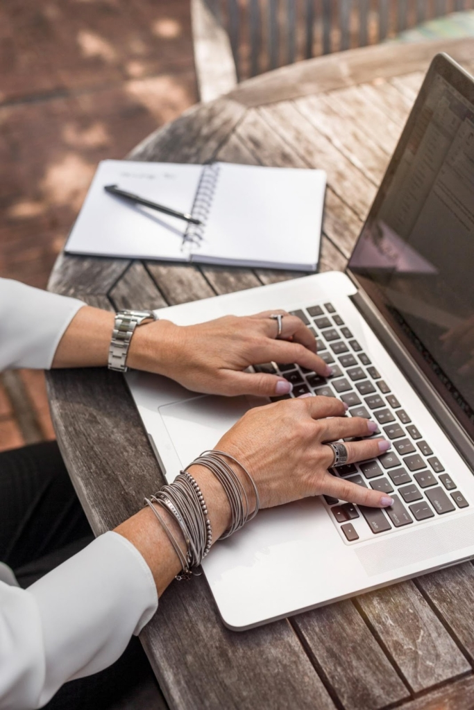 businesswoman hands-on keyboard of a white laptop
